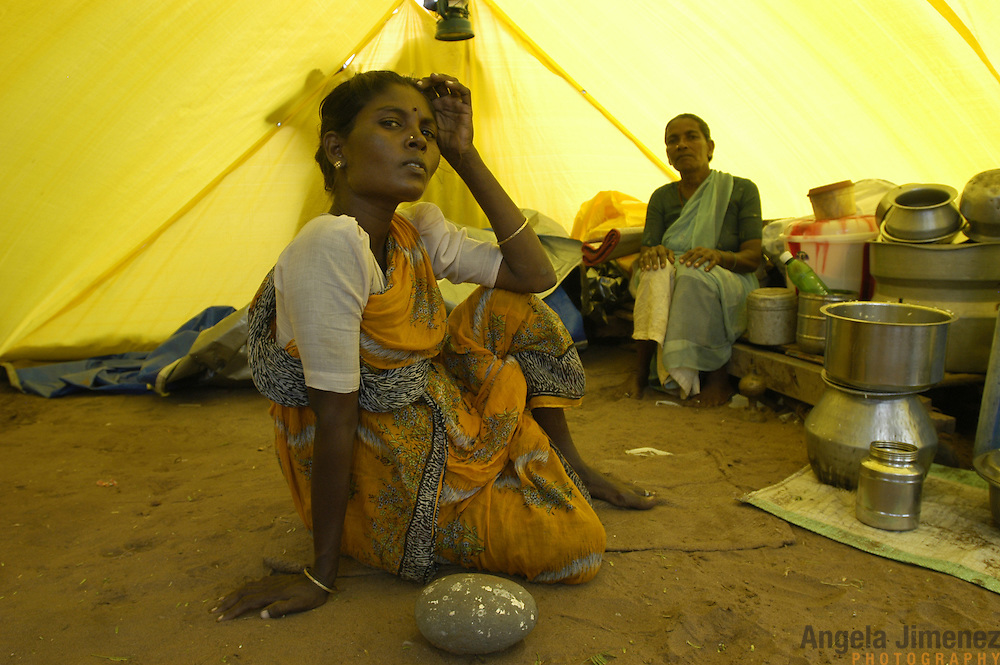 A family is living and storing all their salvaged belongings in a government-issued tent near the beach in the fishing village of Perumalpettai, in Tamil Nadu, India, on January 21, 2005, after their home was swept away by the Indian Ocean Tsunami on December 26, 2004. The tsunami killed 37 villagers and destroyed nearly all of their fishing boats. Generated by an earthquake on the ocean floor, the tsunami devastated the fishing industry along the southeastern coast of India.