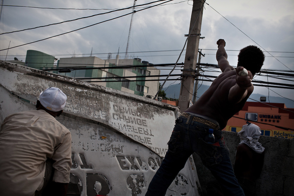 Martelly's supporters demonstrate, in the streets of Port-au-Prince, to protest against the results of the presidential elections and the defeat of their leader, Michel Martelly. /// A Martelly's supporter throws a stone against Minstah's tanks, from a roof of Port-au-Prince.