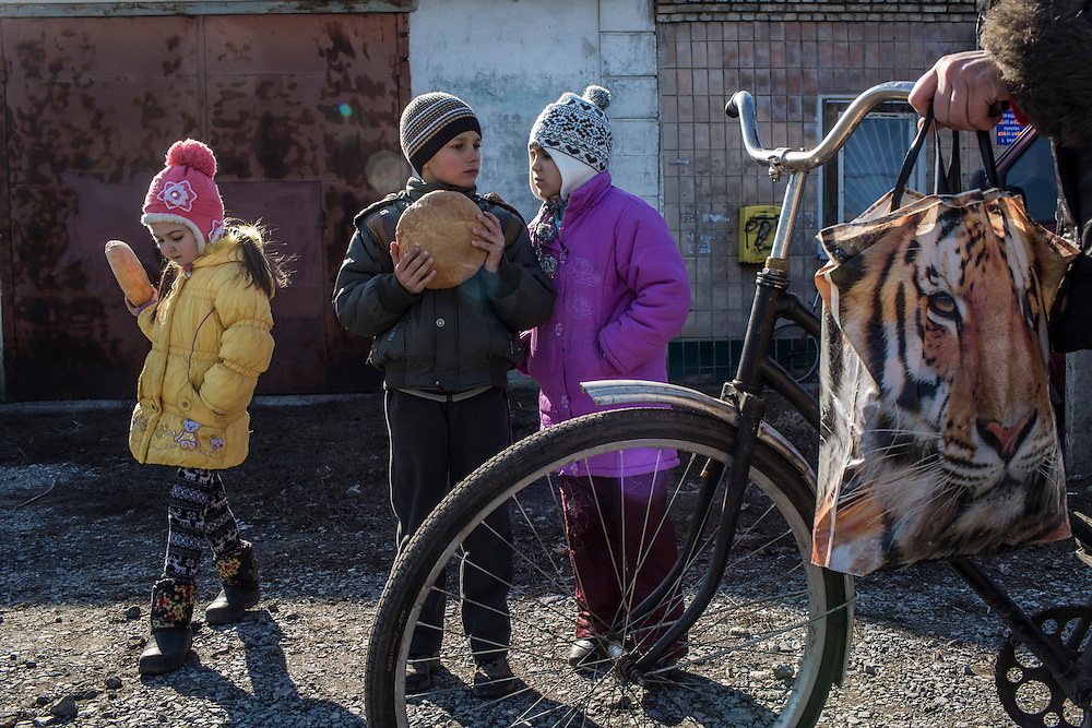 MARIINKA, UKRAINE - FEBRUARY 20, 2016:  Children hold bread distributed as humanitarian assistance by volunteers affiliated with the Christian Help Center of the Church of the Transfiguration in Mariinka, Ukraine. The Donetsk suburb has been the scene of some of the heaviest fighting recently between Ukrainian forces and pro-Russian rebels. CREDIT: Brendan Hoffman for The New York Times
