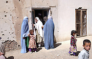 Afghan women and children wait to enter the Charasyab health clinic approximately 20 kilometers outside of Kabul, Afghanistan on Sunday, May 26, 2002.