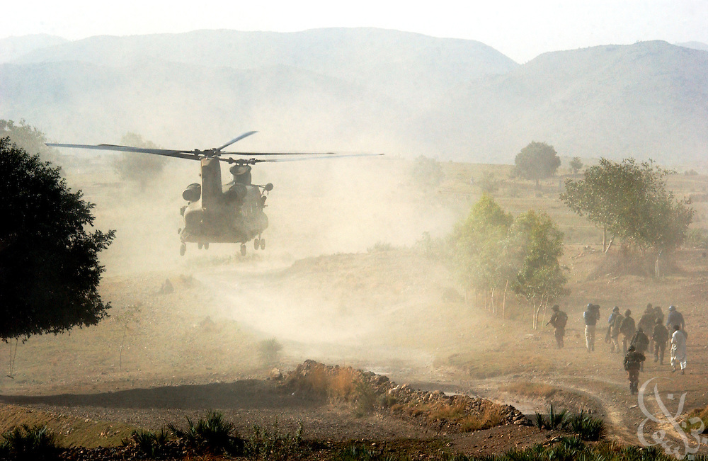 "British Royal Marines of 45 Commando prepare head back to a landing Chinook helicopter during an ""eagle vehicle check point"" (VCP) mission as part of the ongoing Operation Buzzard July 8, 2002 in southeastern Afghanistan. During VCPs, small groups of marines are dropped quickly by helicopters to search random vehicles on dirt roads and trails near the Pakistan-Afghanistan border to deny al Qaeda and Taliban fighters freedom of movement across the region."
