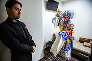Security guard Tom Jones looks on as Beijing Opera actress Sun Ping, gets ready at the back stage before the show, The Drunken Beauty, begins at the Wallis Annenberg Center for the Performing Arts in Beverly Hills, California on January 31, 2015.  Sun, a national first-class actress, member of the international Dramatists Association, dean of the Art Research School of Beijing Foreign Studies University and executive director of the Research Institute on Chinese National Opera at Renmin University. With a history of nearly three hundred years, Beijing Opera is a traditional theatrical art form in China, Its main features include a variety of music, song, dialogue, dance and acrobatics, in addition to its colorful costumes and bold makeup.