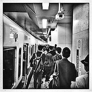 After arriving in Shinjuku Station, passengers are handed off to another security camera watching them get off the train and carry on with their day.  Tokyo, Japan.