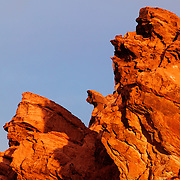 Rugged rock faces are turned red at sunrise in the Valley of Fire, Nevada. The Valley of Fire is Nevada's oldest state park and named for the dramatic sandstone formations that are fire-colored in certain types of sunlight.