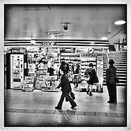 Watching commuters while they shop: Dome-type security camera stands guard over mini-market kiosk in Shinjuku Station.  Tokyo, Japan.