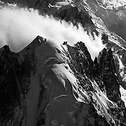 An aerial photograph of the Aiguille Verte and Mont Blanc (in the background) above the Chamonix Valley, France