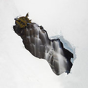 A portion of Myrtle Falls, located in Mount Rainier National Park, Washington, is visible through a melted-out window in a snowy bank.