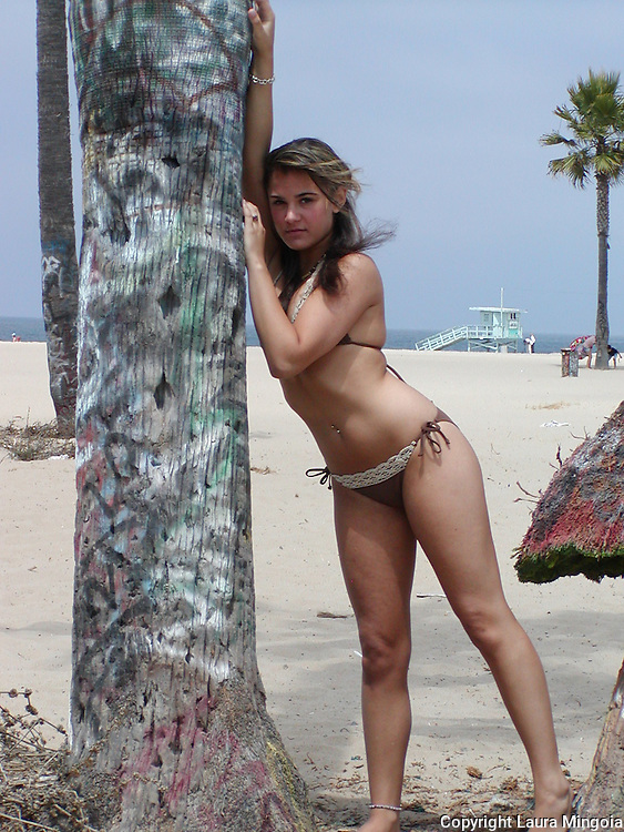 A beautiful young woman, posed upon a palm decorated with grafitti. The photo was in Venes Beach, California
