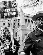 A city deputy sheriff and protestor stands outside the courthouse where William Porter is on trial in Baltimore, Md., December 15, 2015. Porter is one of six police officers charged in connection with the death of Freddie Gray.  Photo by Bryan Woolston / REUTERS .