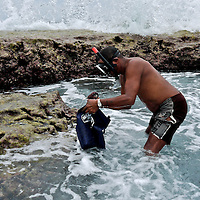 An indigenous Kuna fisherman extracts shells and other animals from the reef. Dutch Keys. San Blas Islands