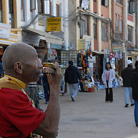 Monk does a MO by  the stupa in Kathmandu.