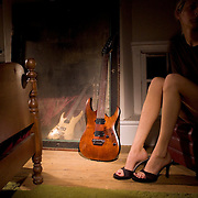 Ibanez guitar leaned up against mirror. Mirror reflecting another Ibanez guitar. Blond woman sitting in chair in the shadows with long legs and a pair of black high heeled mules in the light.