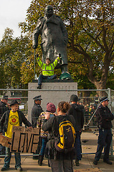 "Parliament Square, London, October 22nd 2014. Protesters from ""Occupy Democracy"" continue their demonstration against what they say is the hijacking of Britain's democracy by capitalism, where big business is allowed to trample people's rights. Having earlier been removed from Parliament square on grounds that they had damaged the threadbare lawn, they continue to demonstrate outside the closed off space. PICTURED: A protester sits on the plinth of Churchill's statue, where he as been for 24 hours, surrounded by police who, it is claimed will arrest him when he eventually comes down."