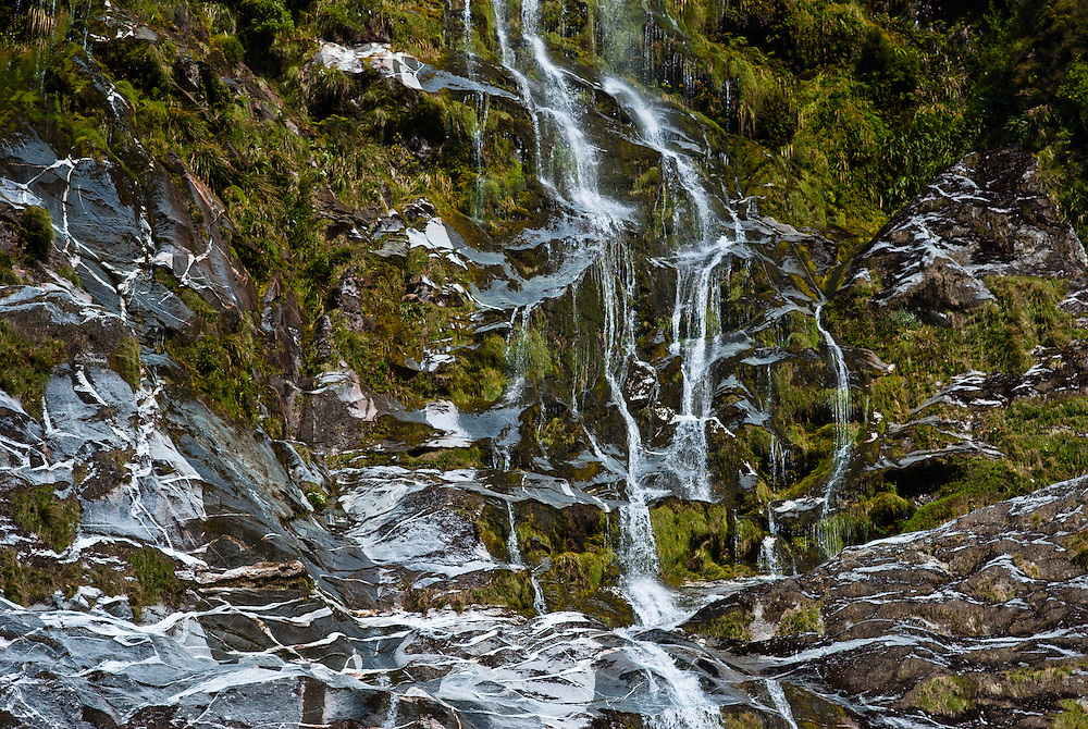 Water cascades over gneiss rock formations and mossy growth in the Clinton Canyon, Milford Track, Fiordland, New Zealand, Fiordland, New Zealand