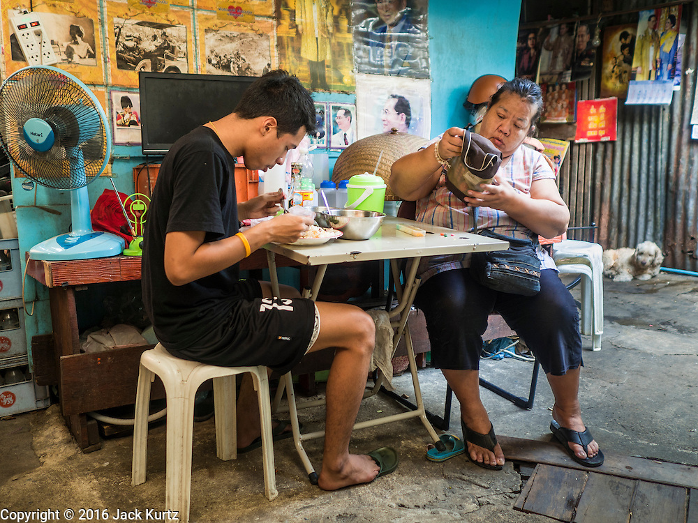 07 APRIL 2016 - BANGKOK, THAILAND: A woman and her son eat their lunch in front of their home in the squatters' community in Mahakan Fort. Mahakan Fort was built in 1783 during the reign of Siamese King Rama I. It was one of 14 fortresses designed to protect Bangkok from foreign invaders, and only of two remaining, the others have been torn down. A community developed in the fort when people started building houses and moving into it during the reign of King Rama V (1868-1910). The land was expropriated by Bangkok city government in 1992, but the people living in the fort refused to move. In 2004 courts ruled against the residents and said the city could take the land. The final eviction notices were posted last week and the residents given until April 30 to move out. After that their homes, some of which are nearly 200 years old, will be destroyed.       PHOTO BY JACK KURTZ