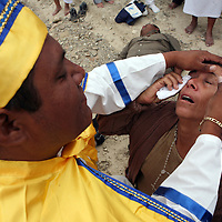 A healer and follower of Nino Fidencio, a curandero or healer who passed away in the 1938, squeezes lime in the eye of a follower as part of a healing just outside of Espinazo, Mexico on Thursday, October 19, 2006. Followers of Nino Fidencio believe that his spirit can posses other healers, who once possessed, speak in child-like voices and perform a variety of medical cures on their followers.  His believers, an estimated 20,000, gather in his hometown for a three-day festival twice a year in March and October. (Photo/Scott Dalton)
