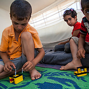Playing Legos in their tent from left to right are Amir, 5, his brother Ibrahim, 7, their cousins Noor, 8, and Abdu Al Rahman, 6. Zaatari Camp for Syrian Refugees, Jordan, August 2013.