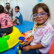 """Abdal Kader, 5, from Daraa, Syria, enjoys the Mercy Corps child friendly space """"Tom and Jerry."""" Azraq camp for Syrian refugees, Jordan, May 2015."""
