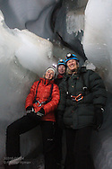 Tourists in April explore ice cave formed inside glacier by annual meltwaters outside Longyearbyen on Spitsbergen island, Svalbard, Norway.