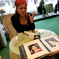 """BEIJING, 12.October : Mrs. Shi Sanba , 54, director of a hospital for plastic surgery, shows photos of her former self at the age of 28 ( see album) in a hospital in Beijing, October 12,  2004, in China. .. ..Plastic surgery gradually is becoming big business in China's capital.  Since this summer , hospitals  have been flooded with teenage patients ever since offers """"special summer reductions"""" for students were made..  ..Whereas in Mao Zedong's China, even pigtails were seen as a sign of vanity (and had to be cut off) , nowadays, urban Chinese women seek about every means in order to distinguish themselves from the masses.  This year Beijing will organize the worl'd first beauty pageant for women had had plastic surgery."""