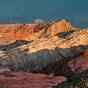 Sunset light illuminates colorful orange, pink, yellow, and white sandstone in White Domes area of Valley of Fire State Park, Nevada, USA. Starting more than 150 million years ago, great shifting sand dunes during the age of dinosaurs were compressed, uplifting, faulted, and eroded to form the park's fiery red sandstone formations. The park also boasts fascinating patterns in limestone, shale, and conglomerate rock. The park adjoins Lake Mead National Recreation Area at the Virgin River confluence, at an elevation of 2000 to 2600 feet (610-790 m), 50 miles (80 km) northeast of Las Vegas, USA. Park entry from Interstate 15 passes through the Moapa Indian Reservation. (Panorama stitched from 19 photos.)