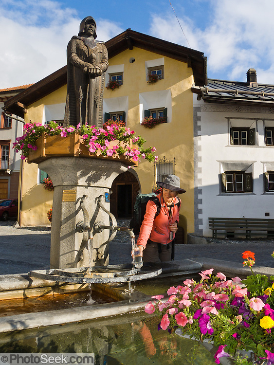 "A traveler fills a water bottle at a fountain decorated with statue and flowers, in Scuol, Engadine, Switzerland, the Alps, Europe. Scuol (or Schuls) is the terminal station of the ""Rätische Bahn"" (RhB), at 1244 meters or 4081 feet elevation in Graubünden canton. The Swiss valley of Engadine translates as the ""garden of the En (or Inn) River"" (Engadin in German, Engiadina in Romansh, Engadina in Italian). Published in Ryder-Walker Alpine Adventures ""Inn to Inn Alpine Hiking Adventures"" Catalog 2006, and in Wilderness Travel Catalog of Adventures 2014."