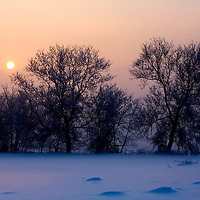 The Sun rises above farm fields off of Hwy 151 north of Columbus, Wisconsin. ..