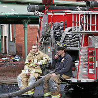 Two fireman relax after a tough night of fire fighting at Eastern Market.