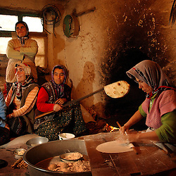 Ali Ipak 's wife Ayse makes bread with her neighbor, Elif (in red)  and daughter Emel, (in blue) as other neighbors Sengul (wearing white and standing)  and Saliha come to show off her new baby, Dudunur December 13, 2005 in central Turkey, Konya in Kutoren district, about 400 kilometers from Ankara.  (Ami Vitale)