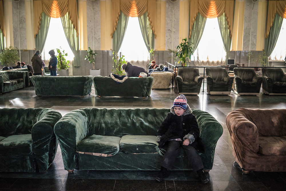 A girl displaced by fighting around the town of Debaltseve sits on a couch in the train station on Thursday, February 12, 2015 in Kharkiv, Ukraine. The group spent several hours in Kharkiv before boarding a train that will take them to Lviv, on the Western side of the country.