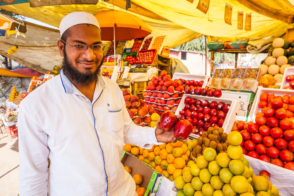 An Indian man in a fruit market in Pune, India holding up apples from Washington State, USA.
