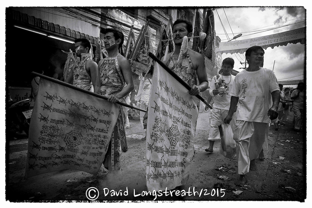 "Devotees to the Chinese Shrine of Ban Tha Rue walk in a street procession in Phuket, Thailand, Sunday, Oc. 18, 2015.  The annual Vegetarian Festival and its accompanying sacred rituals are believed to bestow good fortune on those who practice the religious rites. During the 9 day festival in Phuket Town and surrounding communities which are made up mainly of Chinese desendants, residents observe a strict vegetarian or vegan diet that is suppose to cleanse and grant merit. Sacred rituals where men and women devotees known as ""Mah Song"" or ""Spirit Horses"", work themselves into trances to have all manner of knives, daggers, swords or other items pierced through their cheeks. It is believed that they experience no pain while in the trance. This gruesome from of mortification is what most westerners know of the festival. Devotees also walk barefooted over massive mounds of burring coals and climb ladders that have bladed rungs, all with no effect.  (AP Photo/David Longstreath/str)"