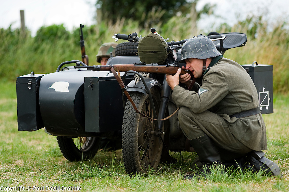 A re-enactor from the Northern World War Two Association Living History group, portraying a Gefreiter of the Panzer-Grenadier-Division Grossdeutschland, takes a firing position with his Mauser K98 rifle behind a BMW R71 motorcycle and sidecar during a large scale battle re-enactment..<br />