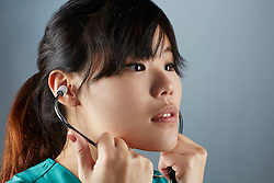 A portrait series representing the intense emotions that Doctors face.  An Asian female Doctor wearing a stethoscope, and green medical scrub suit shown.