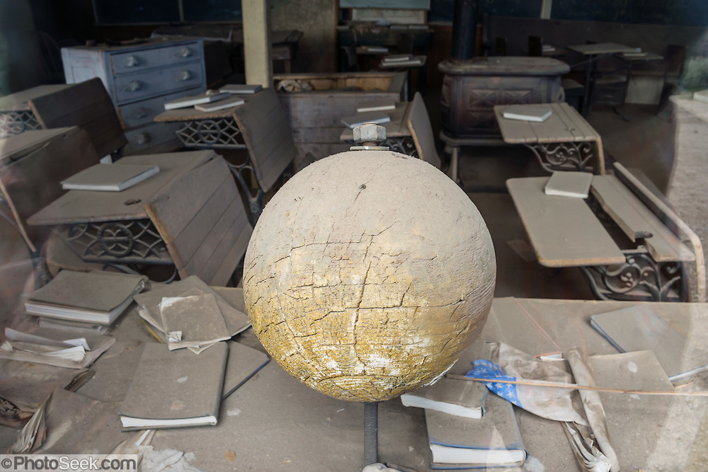 "An old yellowed wooden globe has lost its maps, in Bodie Schoolhouse (which was originally the 1879 Bon Ton Lodging House). Bodie is California's official state gold rush ghost town. Bodie State Historic Park lies in the Bodie Hills east of the Sierra Nevada mountain range in Mono County, near Bridgeport, California, USA. After W. S. Bodey's original gold discovery in 1859, profitable gold ore discoveries in 1876 and 1878 transformed ""Bodie"" from an isolated mining camp to a Wild West boomtown. By 1879, Bodie had a population of 5000-7000 people with 2000 buildings. At its peak, 65 saloons lined Main Street, which was a mile long. Bodie declined rapidly 1912-1917 and the last mine closed in 1942. Bodie became a National Historic Landmark in 1961 and Bodie State Historic Park in 1962."