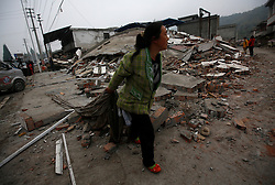 A woman walks by the rubble of a house destroyed by the earthquakel in Lushan County of Ya'an,Sichuan Province, China, 22 April 2013. The Lushan Earthquake in Sichuan Province on 20 April 2013 resulted in 186 people dead, 21 missing, 11248 injured. About 1.72 million people were affected by the quake, while an initial estimate by the International Red Cross on Saturday put the number needing emergency shelter, water and food at 120,000. The China Earthquake Administration (CEA) recorded a magnitude 7.0 earthquake, while the US Geological Survey said it had measured 6.9.