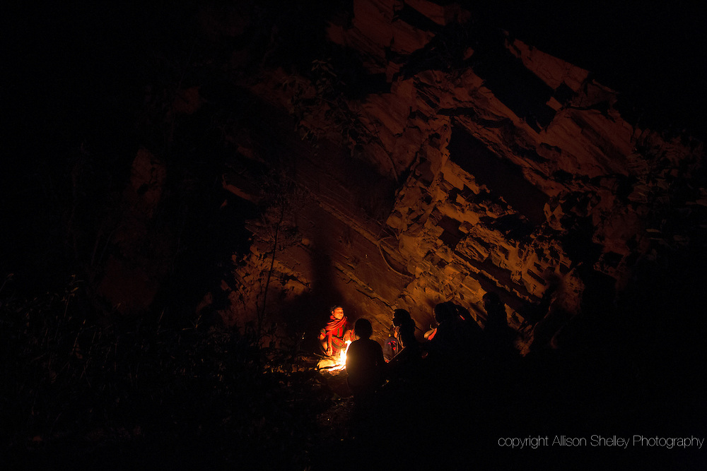 A group of women and girls chat around a fire as they prepare to sleep under a rock outcropping in observance of chaupadi in Kalekanda village, Achham, Nepal.  The space, shared by all of the village women, provides no protection from the elements.