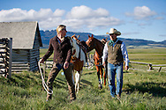 Bryan Ulring, general manager of the J Bar L Ranch, and his wife, Libby Ulring, saddle the horses to herd cattle on June 20, 2012 in the Centennial Valley, near Lakeview, Montana. The J Bar L, a member ranch of Yellowstone Grassfed Beef, works towards economic and ecological sustainability using holistic management techniques. The J Bar L is also a guest ranch, offering visitors a chance to herd cattle and learn about the holistic approach. <br />