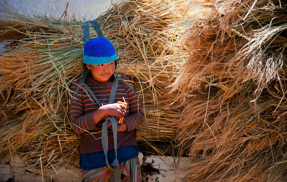 A girl carrying a huge load of hay to stock up for the winter near Paro, Bhutan.