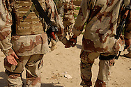 Iraqi army soldiers hold hands during a mission, Iraq, Mar., 12, 2007.