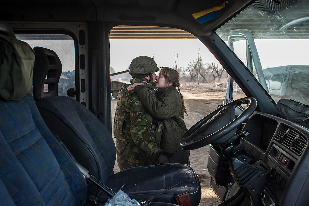 PERVOMAISKE, UKRAINE - MARCH 20, 2015: Volodya, a fighter for the Dnipro-1 battalion, a pro-Ukrainian militia, kisses his wife Natalia after bringing her flowers picked near the front lines at one of the group's bases known as The Bridge near ongoing battles for the town of Pisky in Pervomaiske, Ukraine. CREDIT: Brendan Hoffman for The New York Times