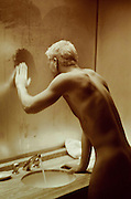 bleach blond man in a steamy bathroom mirror