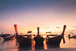 Long tail boats moored along a beach at sunset, Ko Phi Phi Don, Thailand, Southeast Asia