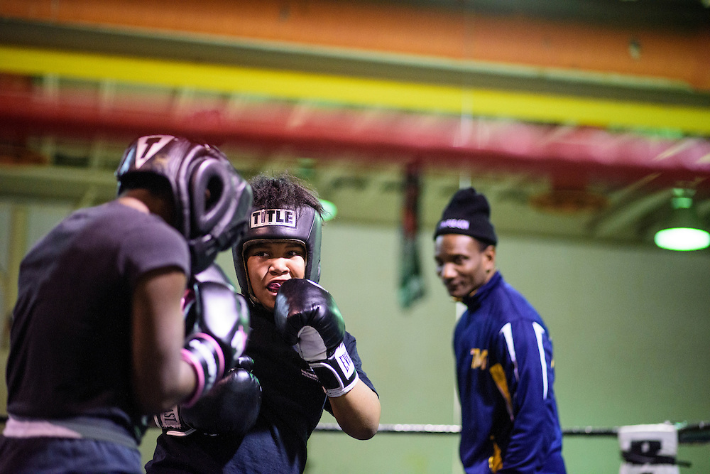 Baltimore, Maryland - January 26, 2017: Kyerianna &quot;lil mama&quot; Foro, 11, spars with Lynnera Spriggs, 15, at the Upton Boxing Club in Baltimore. Coach Calvin Ford watches in the background.<br /> <br /> <br /> CREDIT: Matt Roth for The New York Times<br /> Assignment ID: