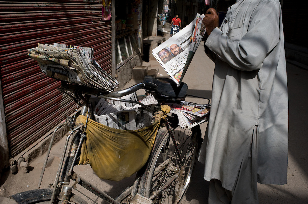 A newspaper delivery man is bringing the day's newspaper after the big news that Osama bin Laden was killed by US special forces in Pakistan. .Lahore, Pakistan, 2011