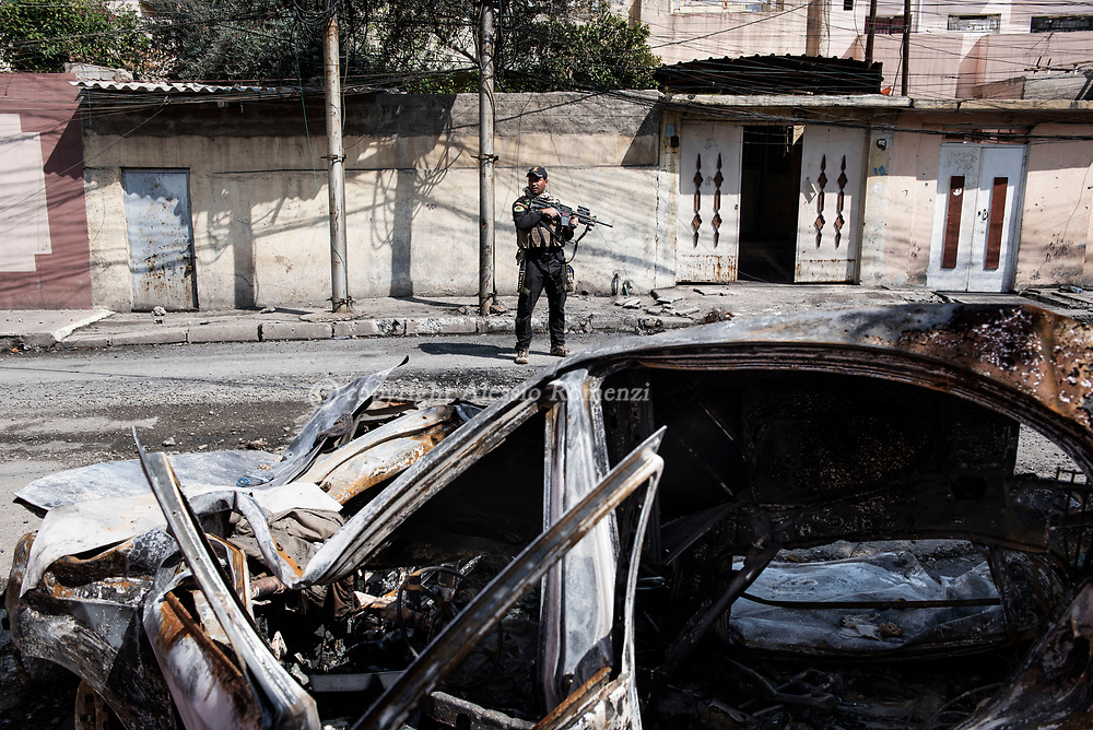 Iraq, Mosul: An Iraqi soldier stands guard in west Mosul. Alessio Romenzi