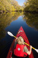 A boy kayaking on Concord River with fall reflection.