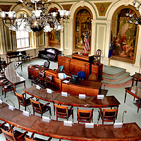 New Hampshire State House Senate Chamber in Concord, New Hampshire<br /> There are four impressive paintings within arches at the front of the 24 member Senate Chamber at the New Hampshire State House in Concord. Three are shown here. On the left is Dartmouth College&rsquo;s first graduation. In the center is Daniel Webster reading the Constitution. On the right is Abbott Thayer teaching an art class. He was called the &ldquo;father of camouflage.&rdquo; Behind him is the image of an angel. This is how he often portrayed women in his famous art.