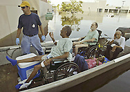 Patients of the United Medical Rehabilitation Hospital, who are either in wheelchairs or cannot walk, are loaded into a boat after they were rescued from the flooded hospital in New Orleans East August 31, 2005. Authorities struggled on Wednesday to evacuate thousands of people from hurricane-battered New Orleans as food and water grew scarce and looters raided stores, while U.S. President George W. Bush said it would take years to recover from the devastation.
