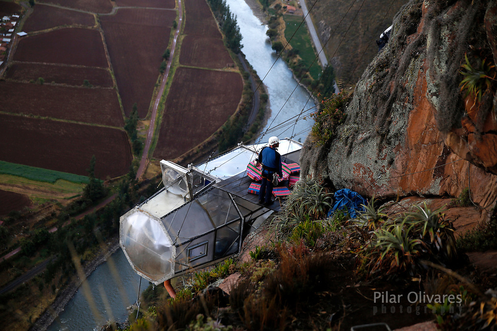 """A guide waits for guests above the sleeping pod at the Skylodge Adventure Suites in the Sacred Valley in Cuzco, Peru, August 14, 2015. Tourists taking on an arduous climb up the steep cliff face of Peru's Sacred Valley are being rewarded for their efforts by being able to spend the night in transparent mountaintop sleeping pods at the """"Skylodge Adventure Suites"""". To reach the pods, visitors need to climb 400 metres of via ferrata (a steel cable and rungs) up the valley side or hike an intrepid trail through zip lines. REUTERS/Pilar Olivares"""